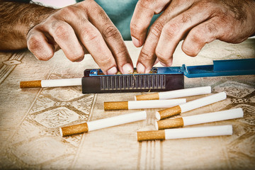 Male hands making cigars with tobacco