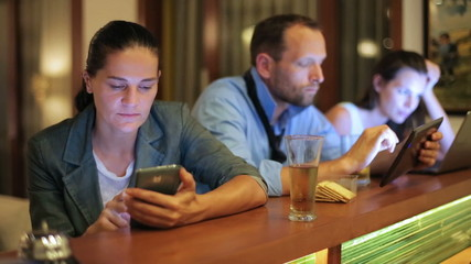 Businesspeople working on modern technology in pub at night