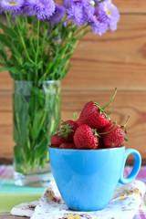 Fresh strawberries in a blue cup