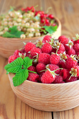 Raspberries and currants in wooden bowls