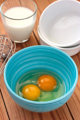 Eggs in a blue bowl and a glass of milk