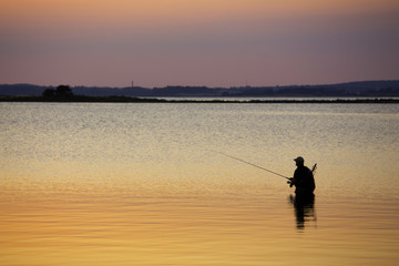 Man standing in water fishing