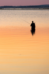 Man standing in water fishing