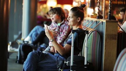 Mother waiting with son for airplane and talking on cellphone