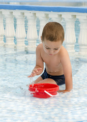 Child playing in water pool