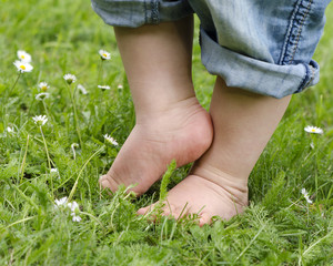 Child feet on grass