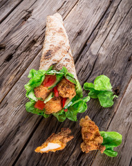 Chicken strips in a Tortilla Wrap on wood.
