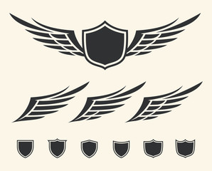 Vector set of isolated winged crests over white background.