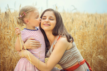 Young mother with cute daughter at grain field