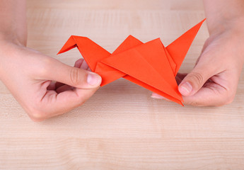 Hands holding origami crane on wooden table