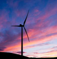 Wind turbine sunrise, dawn. Clean energy background.
