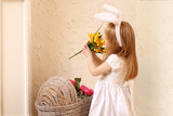 Little beautiful girl in dress and bunny ears sniffs flower poster