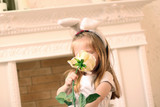 Little beautiful girl in white dress and bunny ears sniffs poster