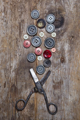 Old scissors and buttons on the wooden table