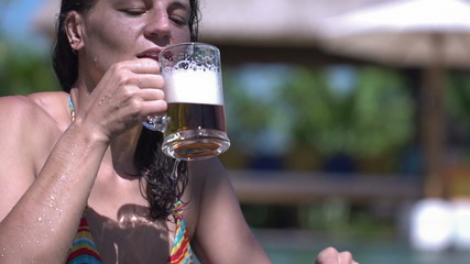 Woman drinking beer in pool, slow motion shot at 240fps