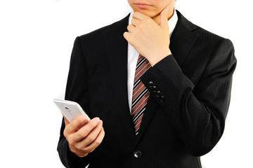 スマートフォンを操作するスーツのビジネスマン