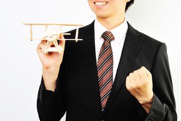飛行機の模型を持っているスーツのビジネスマン