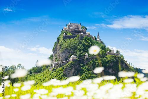 Leinwandbild Motiv Hochosterwitz castle behind chamomile flowers