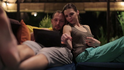 Relaxed couple sitting on couch and using laptop