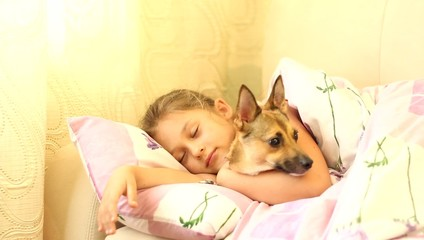child and puppy under blanket
