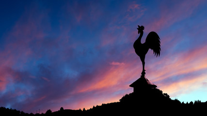 Spectacular dawn with cockerel weathervane and landscape.