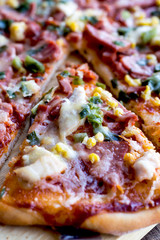 pizza with sausage, chicken, corn and cheese