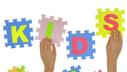 "Hands forming word ""Kids"" with jigsaw puzzle pieces isolated"