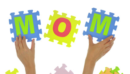 "Hands forming word ""Mom"" with jigsaw puzzle pieces isolated"