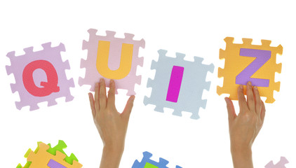 "Hands forming word ""Quiz"" with jigsaw puzzle pieces isolated"