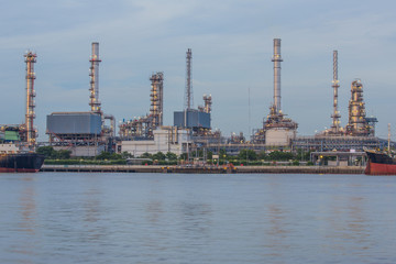 Oil refinery plant along the river before sunset