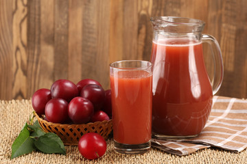 plum juice in a glass and pitcher, plums in a wicker basket on a