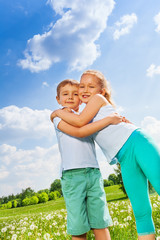 Funny kids hugging together on a meadow