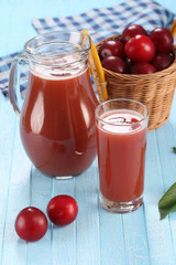 plum juice in a glass and pitcher, plums in a wicker basket