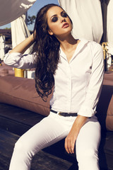 sexy brunette in white shirt and pants posing on beach