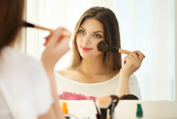 Beauty woman looking in the mirror and applying makeup