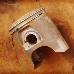 Damaged piston with intake valve on a white wooden table