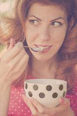 Pin-up girl eating ice cream, looking away
