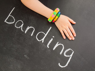 childs arm with loom band bracelets on a blackboard