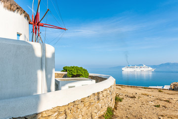 Traditional windmill with a cruise ship moored in the bay of Myk