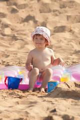 Девочка играет в песок на берегу моря