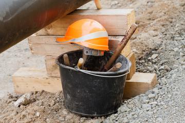 Stillleben auf der Baustelle - Ein Eimer mit Werkzeug und Helm
