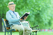 Senior gentleman reading book in park seated on bench