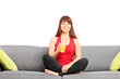 Woman drinking a juice seated on sofa