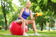 Young woman exercising with a dumbbell and pilates ball