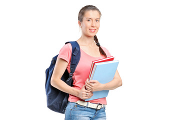 Schoolgirl with backpack holding notebooks