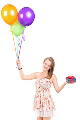Woman holding a present and a bunch of balloons