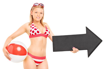 Woman in bikini holding a beach ball and an arrow pointing right