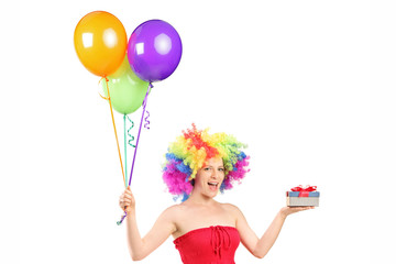 Woman wearing a wig and holding a present and a bunch of balloon