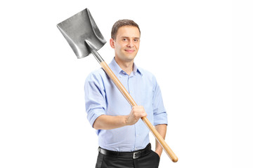 Young man posing with a shovel