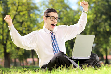 Young man cheering and watching TV on a laptop in park